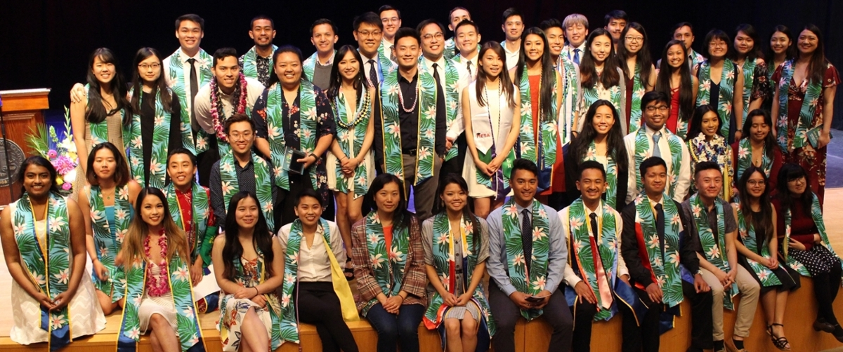 A group of smiling graduating students posing for a photograph, wearing AA/PIRC sashes.